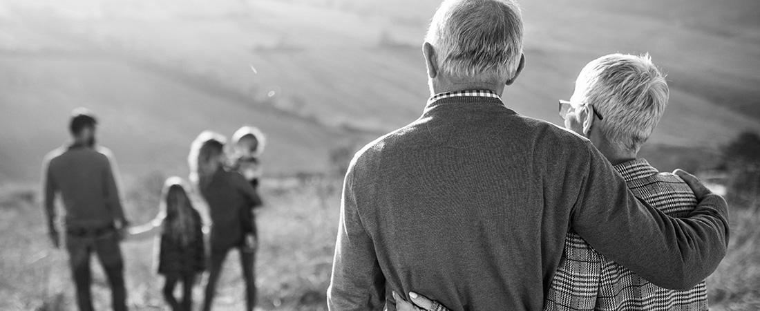 An elderly couples looks on at their children and grandchildren